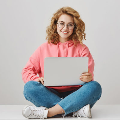Help me with homework. Portrait of happy interesting girl with curly hair, working on project, sitting on floor with crossed legs, holding laptop and smiling broadly, freelancing over gray background.